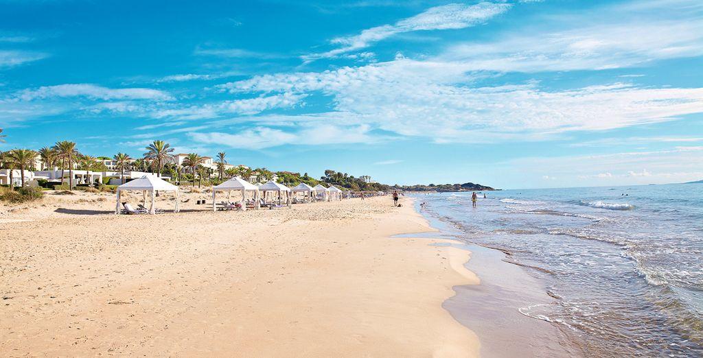 Una playa de arenas doradas rodeada de las aguas cristalinas del mar Jónico...