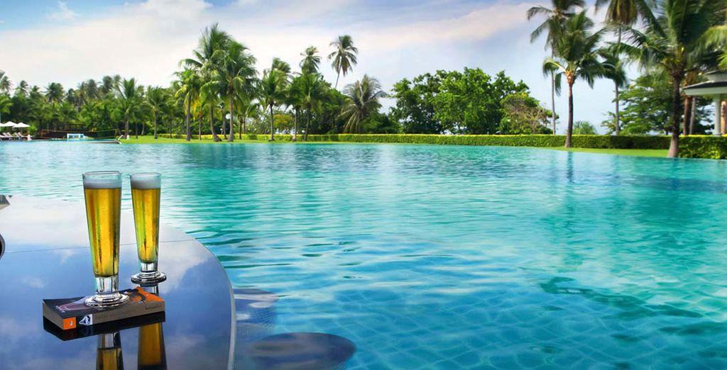 Siéntese a descansar con una bebida a la vera de la piscina