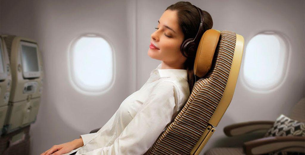 Acomódate y relájate en tu amplio y acogedor asiento con reposacabezas ajustable y almohadas de gran confort