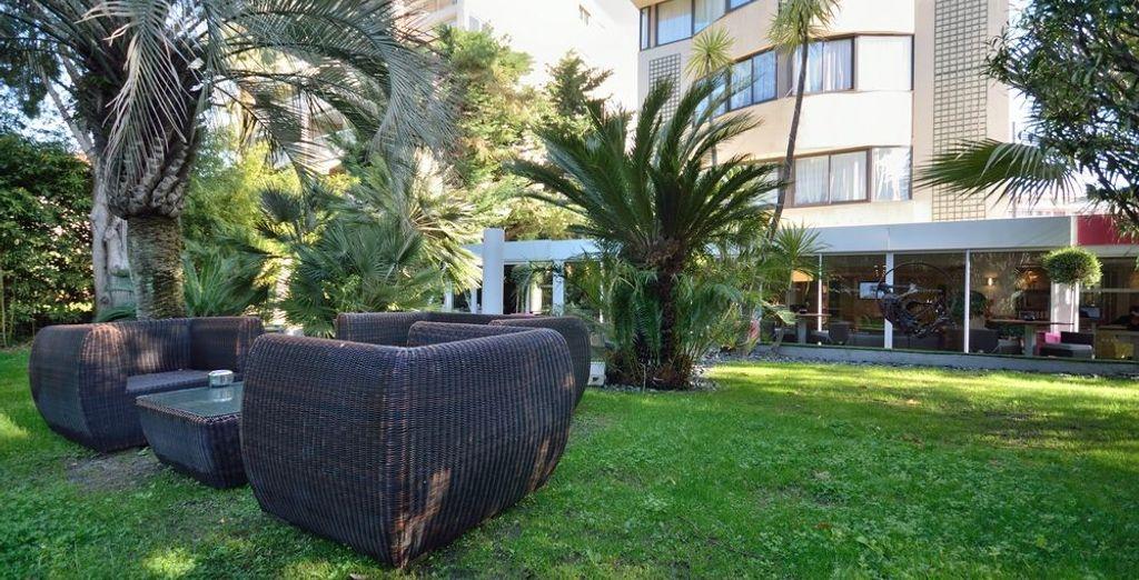 Of in de prachtige aangrenzende tuinen van het hotel