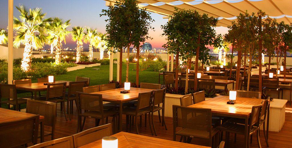 Geniet van een drankje op het terras dat uitkijkt over Abu Dhabi ...